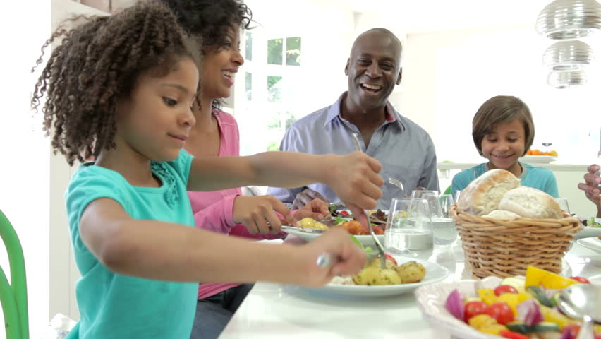 Extended African American family sitting around table at home eating meal together.Shot on Canon 5d Mk2 with a frame rate of 25fps