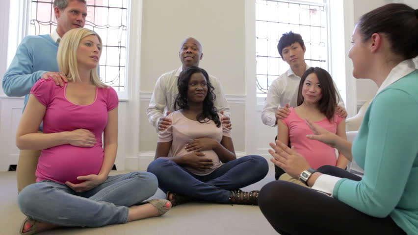 Group of pregnant women with partners practising breathing in ante natal class.Shot on Canon 5d Mk2 with a frame rate of 25fps