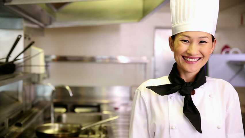 Happy chef smiling at camera holding her hand out in presentation in commercial kitchen - HD stock video clip