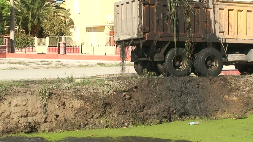 Silt from dredged canal leaking from lorry (wider shot) - HD stock footage clip