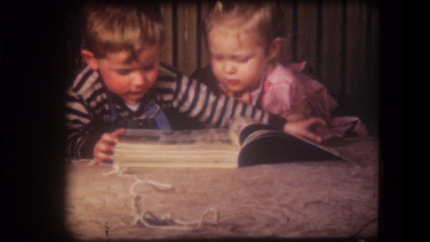 UNITED STATES - CIRCA 1950s: Old home movie film: A girl and a boy reading book and kiss