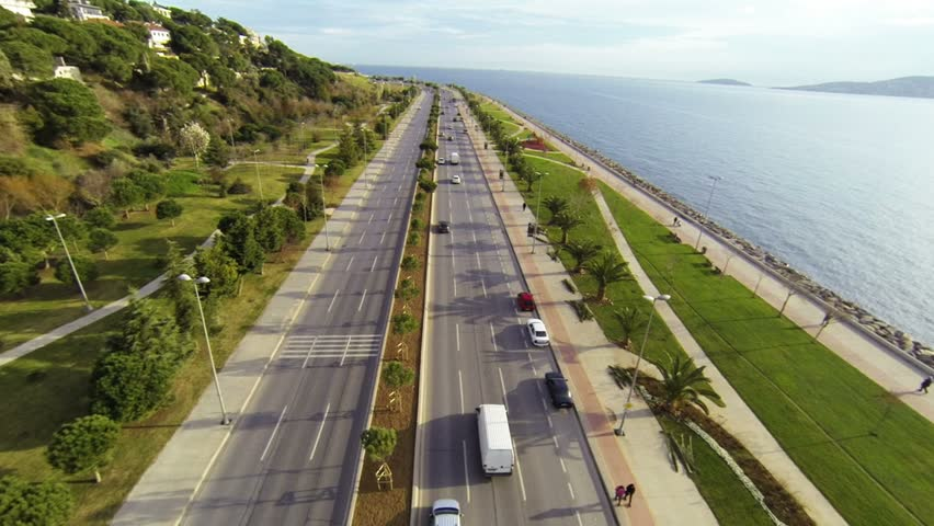 Car traffic on a typical dual carriageway. Coast way from above at Maltepe. Driving to nature on divided highway in a sunny day.