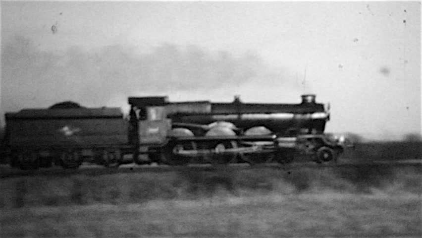 Digital copy of a Great Western steam railway locomotive at speed with a passenger train in a grainy old black and white film in the 1960s in Northamptonshire UK