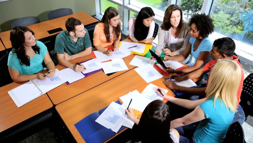 Modern Classroom Students : Male female multi ethnic teenagers sitting around table
