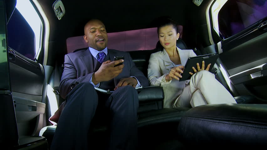 Corporate multi ethnic business leaders using wireless tablet smart phone technology while being chauffeur driven in luxury limousine