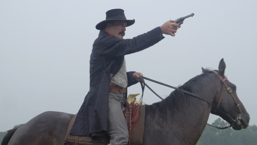 VIRGINIA - 2013.  Western era, Old West Cowboy, Marshall, Sheriff, Outlaw on horseback.  Circa 1860-1890s.  Firing Colt revolver pistol with black powder smoke.  Cowboy Shoot-out, gunplay