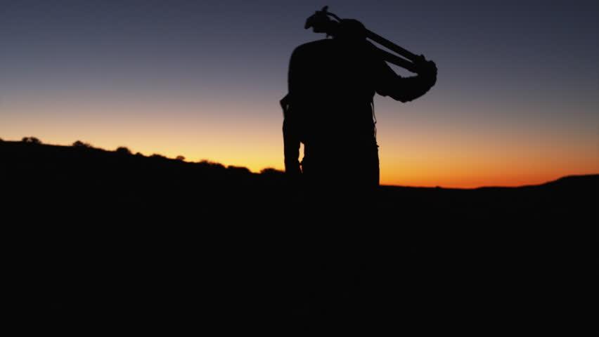 Wide Shot PAN Silhouette of photographer walking, carrying tripod in desert at sunset / Moab, Utah, USA