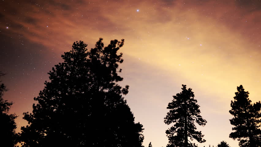 Time Lapse of Stars over Red Clouds and Alpine Forest at Night -Pan-