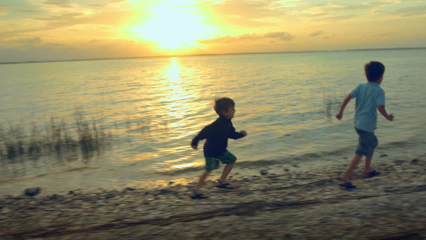 Two little boys running on the shore of a peaceful lake at sunset. 4k Footage - 4K stock footage clip