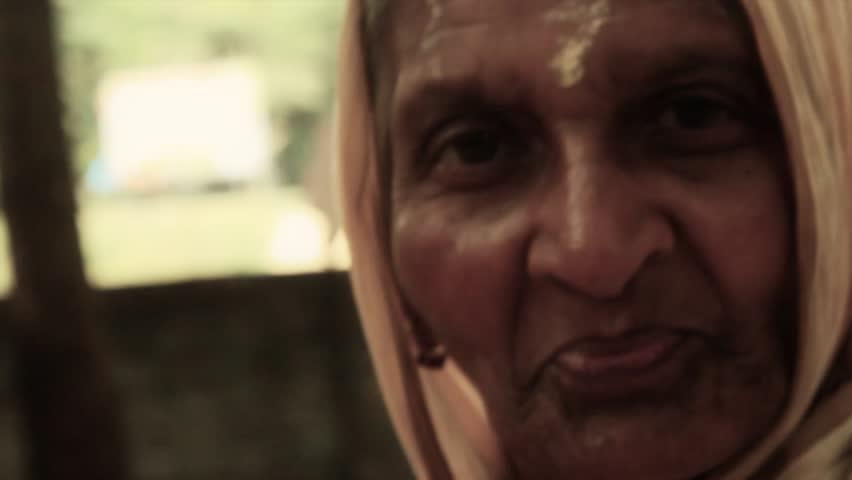 A sweet old Indian village lady gives a subtle, wise smile for the viewer.  Filmed in Navadvipa, Bengal, India in 2014. HD 1920 by 1080. Close up. Still shot.