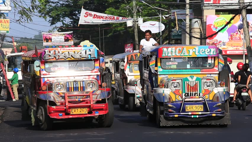 LEGAZPI, PHILIPPINES - MARCH 17 2014: Jeepneys passing, Filipino inexpensive bus service. Jeepneys are the most popular means of public transportation in the Philippines.