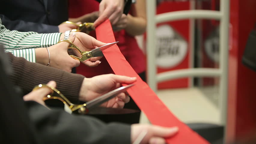 Opening. Ceremonial red ribbon cutting. Scissors in hands.