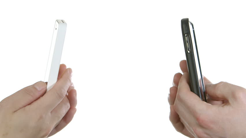 A woman texts on a white cellphone, and a man texts back on a black cellphone. Copyspace in the middle allows for compositing graphics or text.