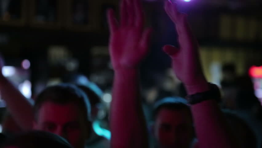 crowd at a rock concert in a bar dancing near the stage and raised his hands up