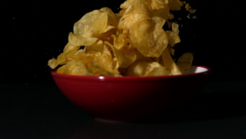 Chips falling into bowl on black surface in slow motion