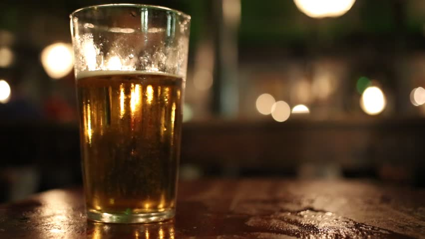 Pint glass of lager on pub table picked up and put down