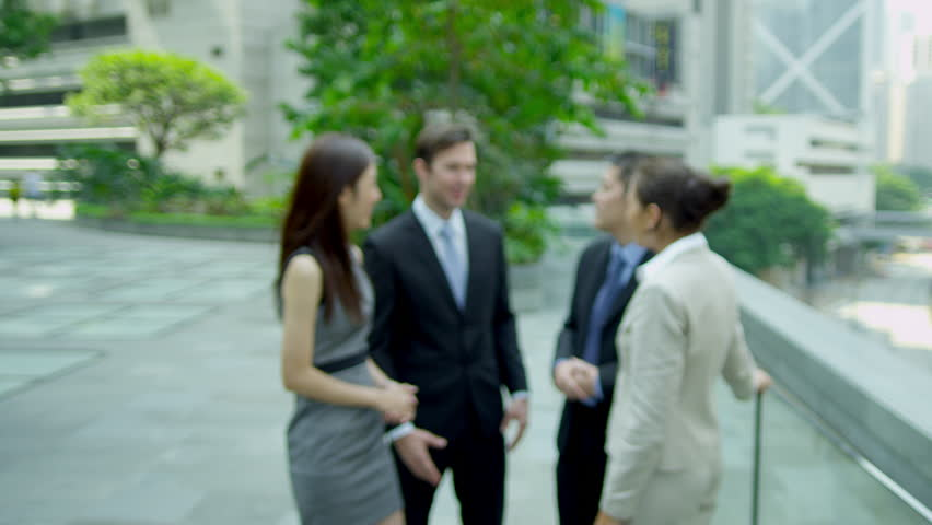 Team multi ethnic corporate management meeting outdoors modern city offices young female Asian Chinese colleague smiling camera foreground shot on RED EPIC