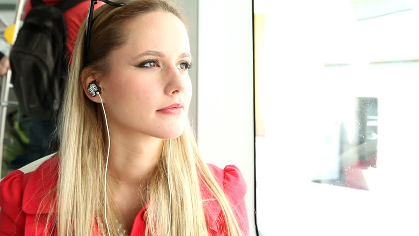 Young beautiful blond woman riding tram, listening to music and dancing