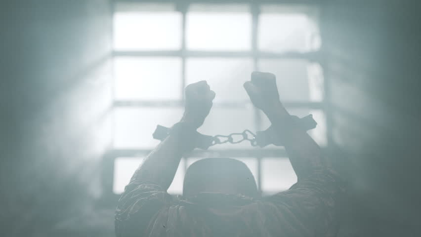 Prisoner with chained hands pray to the Lord. View trough prison window. Dolly shot.