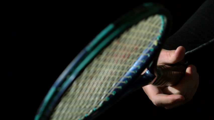 Hand spinning a tennis racket on black background in slow motion - HD stock footage clip