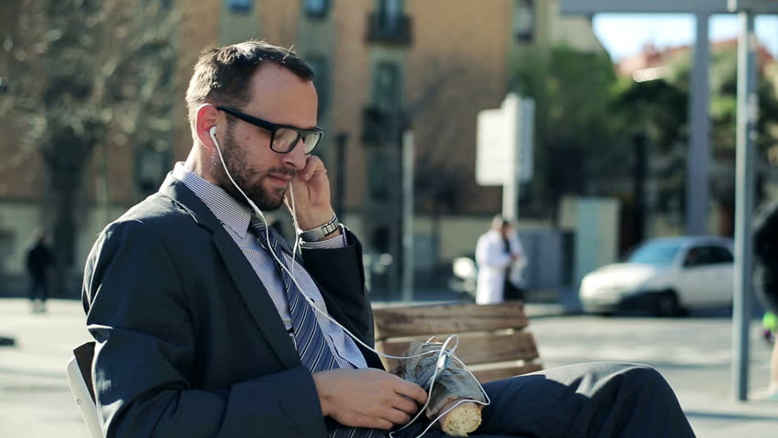 Businessman listening music on smartphone and eating baguette in the city