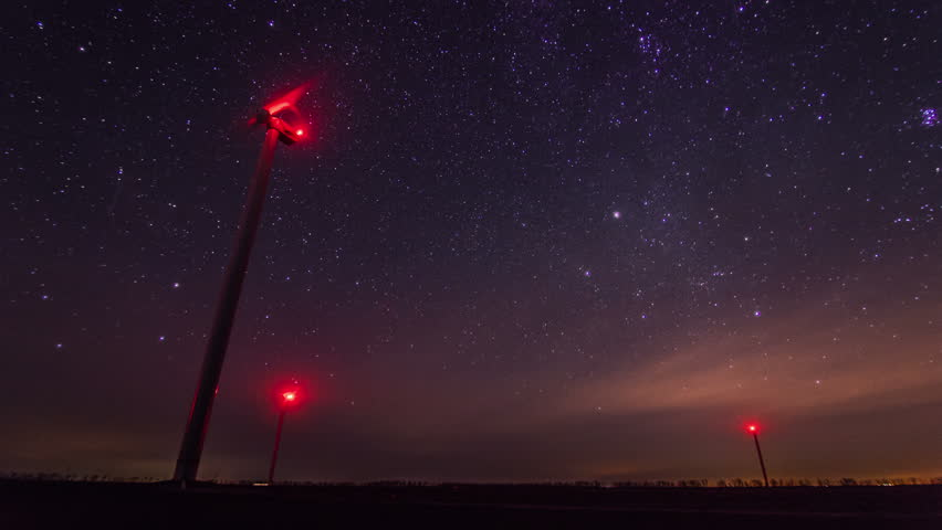 4K. Wind turbines generating power at night timelapse with rotating starry sky on a background