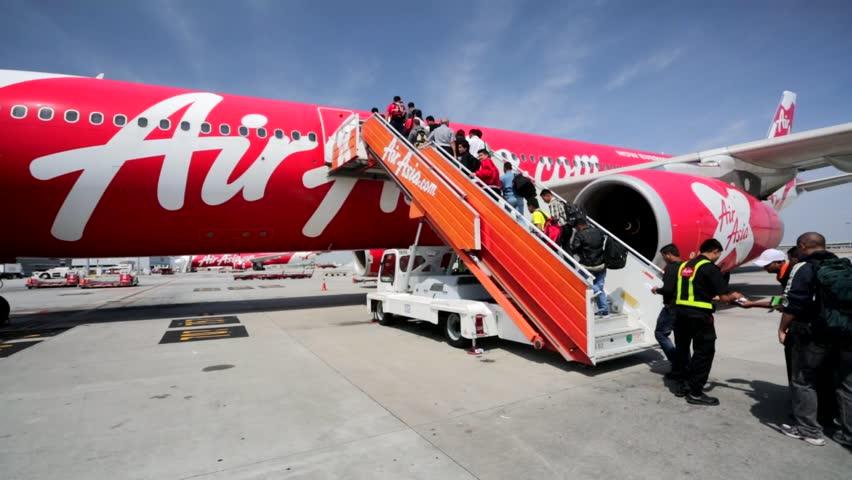 KUALA LUMPUR, MALAYSIA - CIRCA FEB 2014: Passengers board in Air Asia plane in Kuala Lumpur international airport. AirAsia is a Malaysian low-cost airline headquartered in Kuala Lumpur, Malaysia.