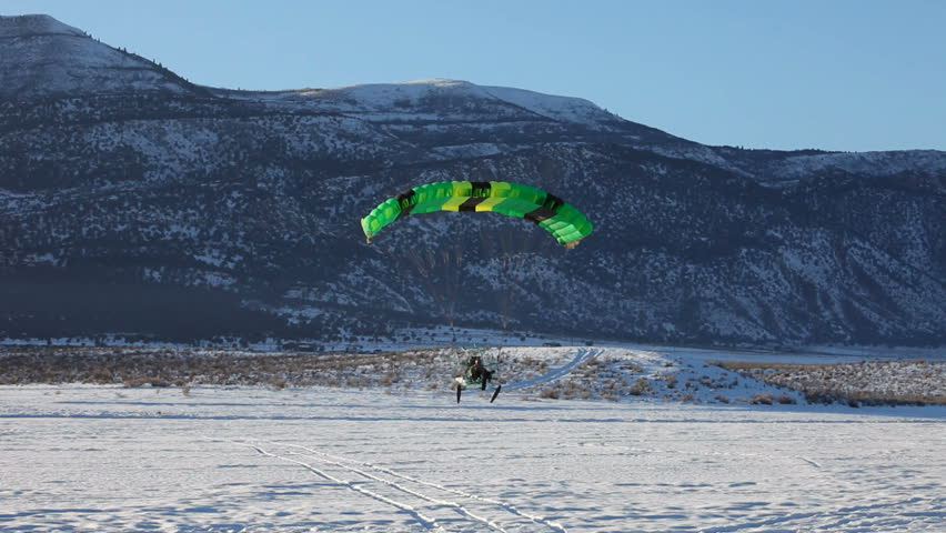 Powered parachute landing past friends on ice and snow covered lake in winter. Central Utah winter recreation and sport. Pilot in aircraft and friends watching. - HD stock footage clip