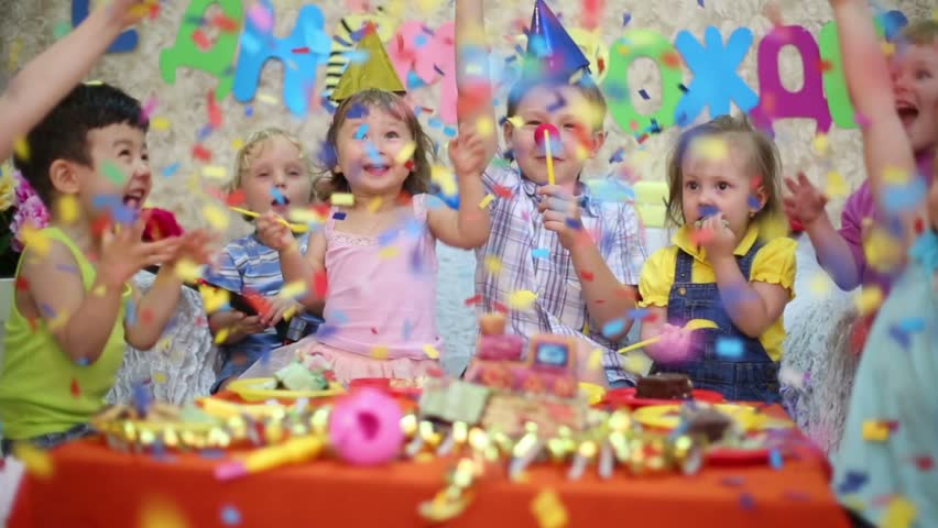 Seven little kids sit at red table with cake and throw confetti at birthday party. Inscription Happy Birthday on wall