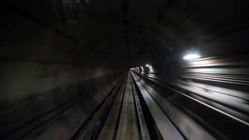 View of a subway tunnel as seen from the front of a moving train.