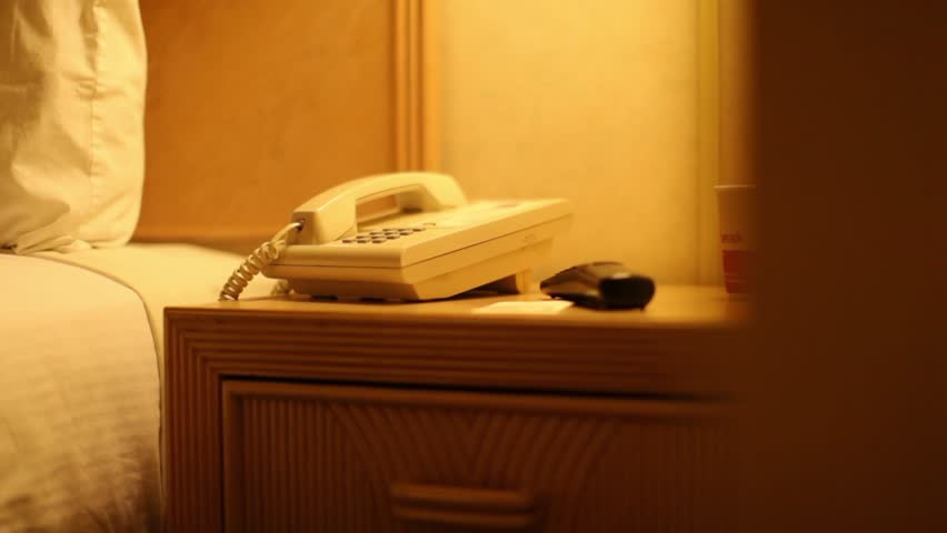 Telephone in a budget motel room along side the bed.