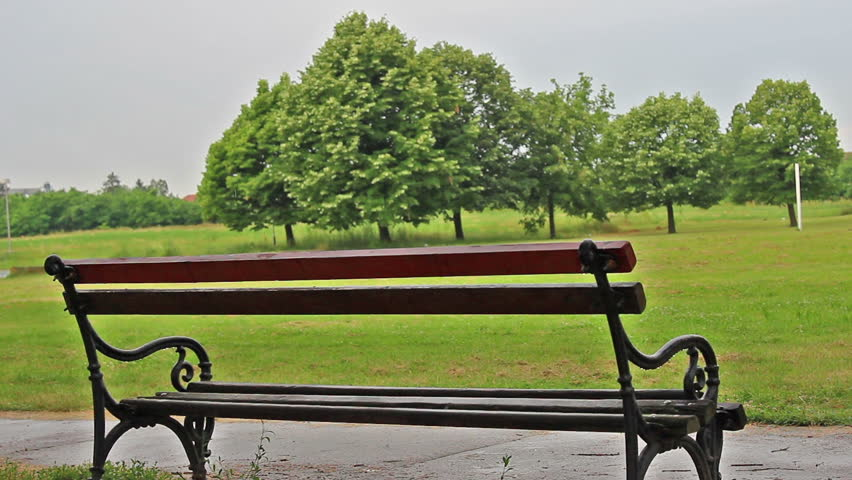 Man approaching bench and sit while raining.