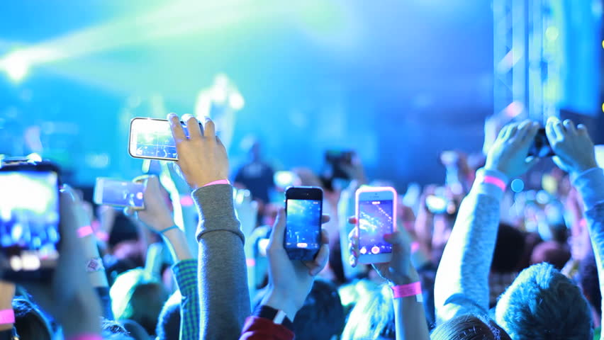 Fans waving their hands and hold the phone with digital displays the crowd at a rock concert.