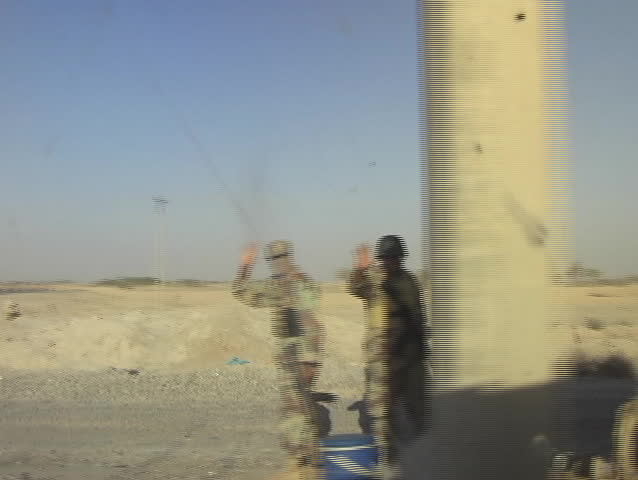 Iraq, Circa 2005: Passing shot of terrain and Iraqi soldiers guarding the gate to a Military Base in Iraq, Circa 2005