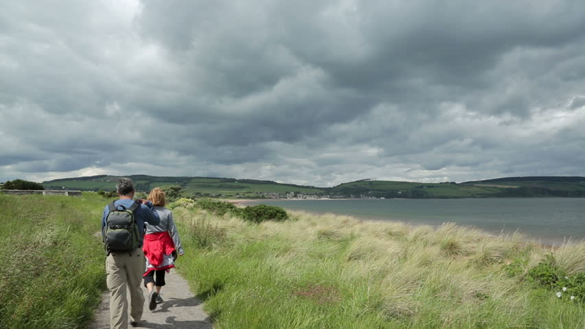 FORTROSE, HIGHLANDS/UK - MAY 14, 2014: Unidentified people walk along the coast path at Chanonry Point on the Moray Firth near Inverness, Scotland. Visitors come here to see the bottle nose dolphins.