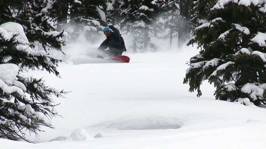 Snowboarder carving fresh powder snow, short montage, some slow motion.
