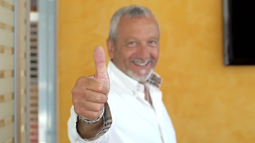 say yes or ok with gesture of hand: businessman makes positive gesture thumbs up