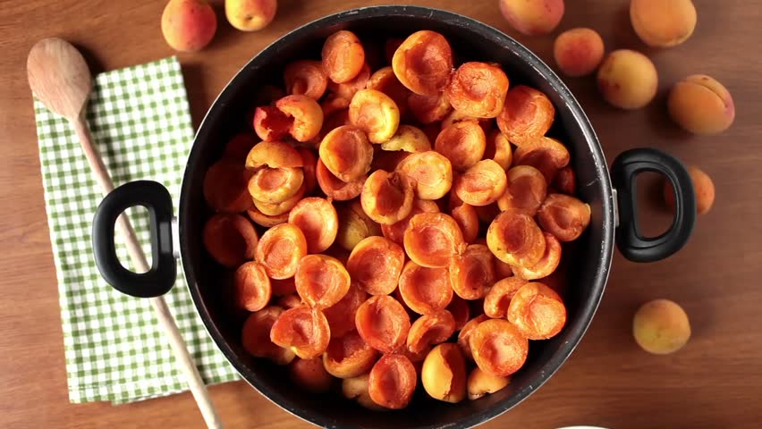 Preparation of apricots jam; video of pouring sugar above the fresh apricots.