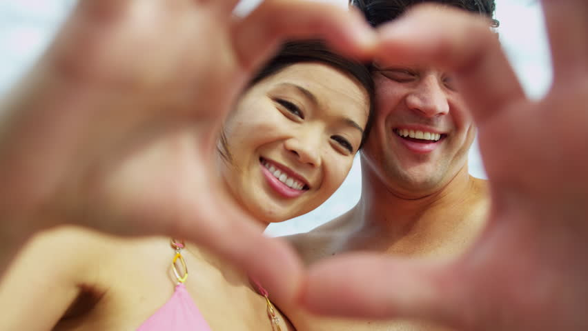 Head shoulders happy attractive young Asian Chinese couple swimwear close up hands heart shape laughing camera fun beach vacation messaging friends social media shot on RED EPIC