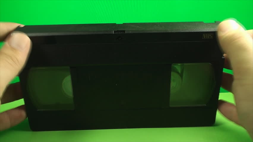 Hand Opening The Latch From A Vintage VHS, Exposing Tape, On A Green Screen