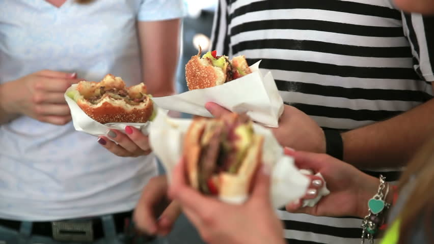 Young people eat burgers and fries on the street