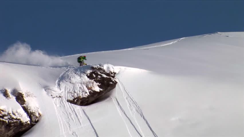 A skier jumps off a rock, does a 360 and lands down the slope without losing balance