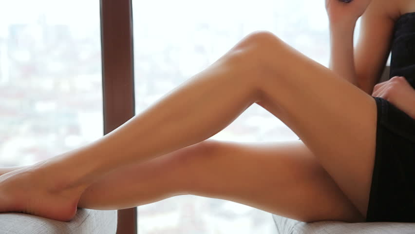 sexy woman applying cosmetic cellulite cream to leg at home