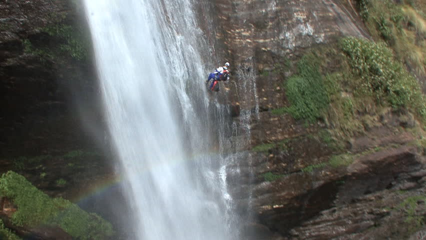 A canyoneer abseils down a waterfall into a canyon