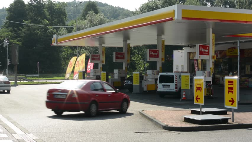 PRAGUE, CZECH REPUBLIC - AUGUST 14, 2014: gas station (oil pump) Shell in the city - with cars and people. Passing cars with forest in the background