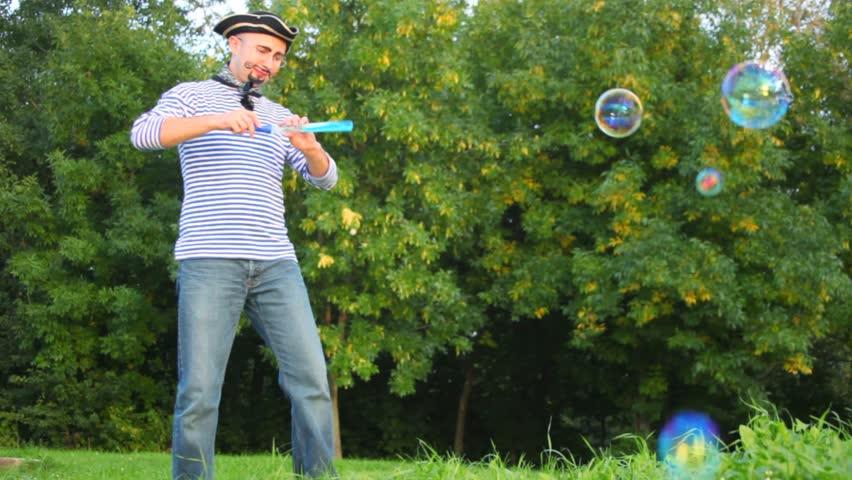 man in pirate costume makes soap bubbles in park  - HD stock video clip