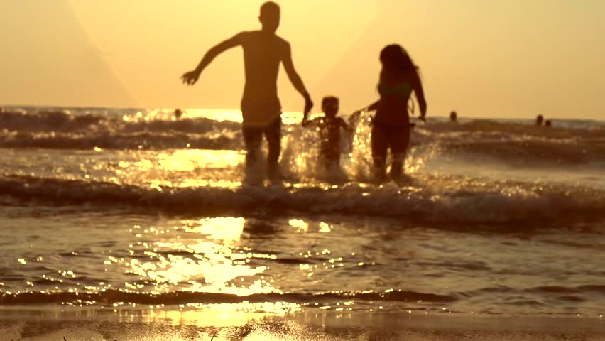 Happy family with a child on vacation at the beach. Smiling Parents with a Little daughter Have a Fun running out of the Sea Splashing and Holds Child By Arms. Over sunset. Slowmotion 240fps 1920x1080 - HD stock footage clip