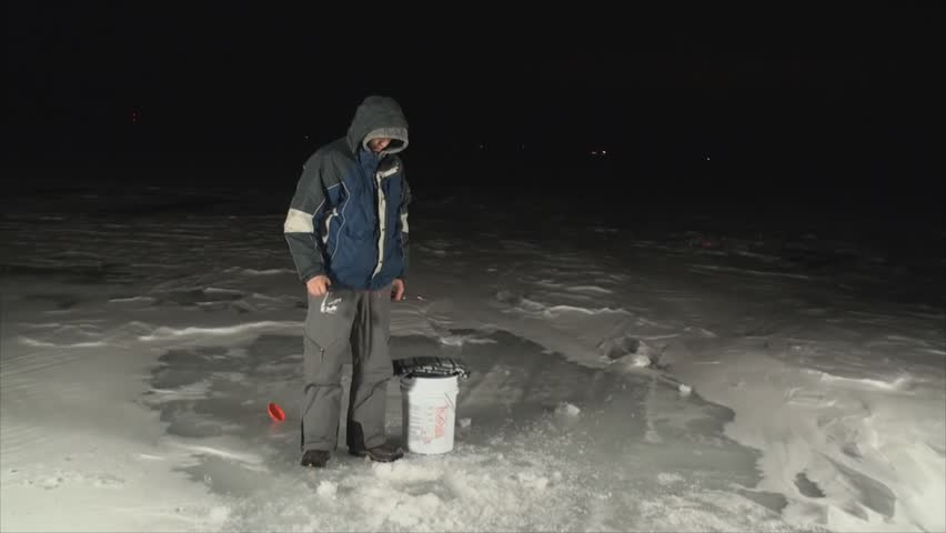 man ice fishing at night on frozen lake 7 stock footage