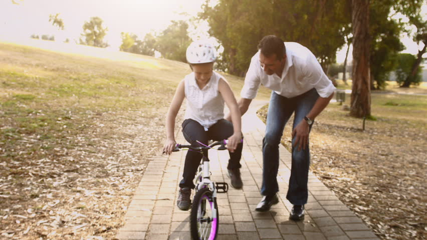 Father teaching daughter to ride her pink bike, steadicam shot.  - HD stock footage clip