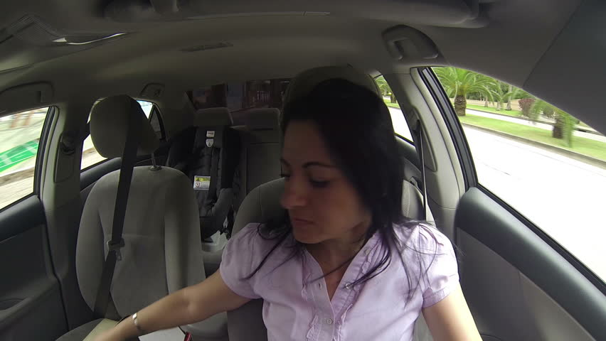 woman applying perfume on her body while driving the car